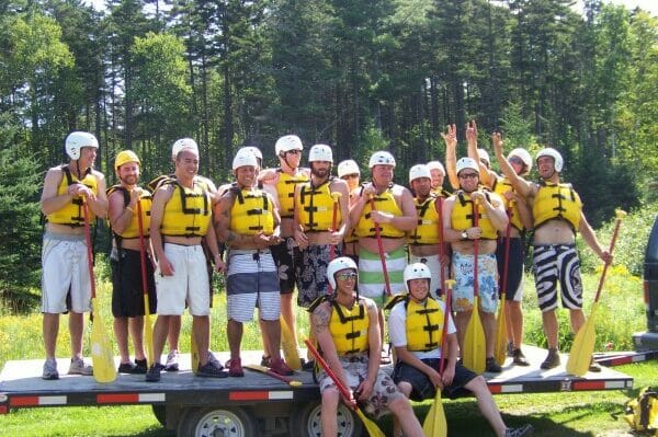 Group of People on a Trailer Smiling With Whitewater Rafting Gear On