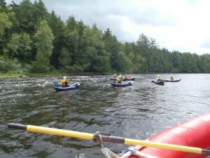 Group of People Kayaking on a River